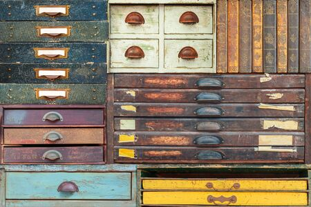 Colorful assortment of vintage wooden drawers and books with labels and handles
