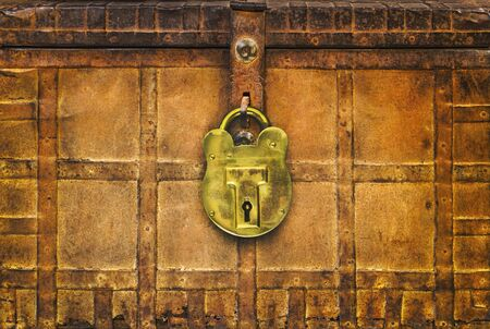 Retro styled image of an ancient locked rusted treasure chest with large brass lock