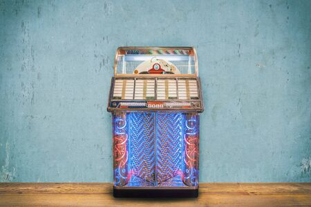 Colorful vintage jukebox in front of a blue weathered wall on a wooden floor