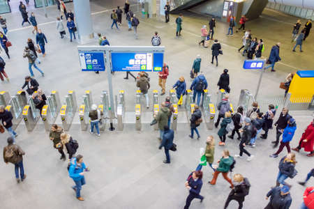 The Hague, The Netherlands - January 15, 2020: Commuters checking in and out for train travel inside the central station in The Hague, The Netherlands Éditoriale