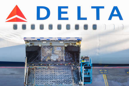Schiphol, The Netherlands - January 16, 2020:  Loading of a cargo container on board of a Delta Airlines airplane on Schiphol Airport, The Netherlands