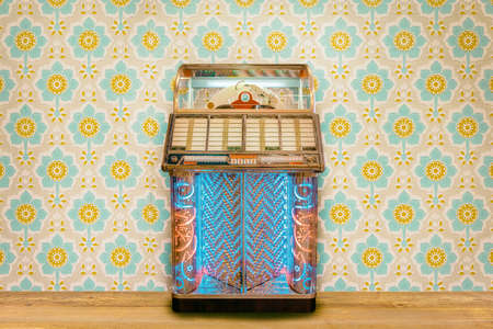 Colorful vintage jukebox in front of retro flower wallpaper on a wooden floor