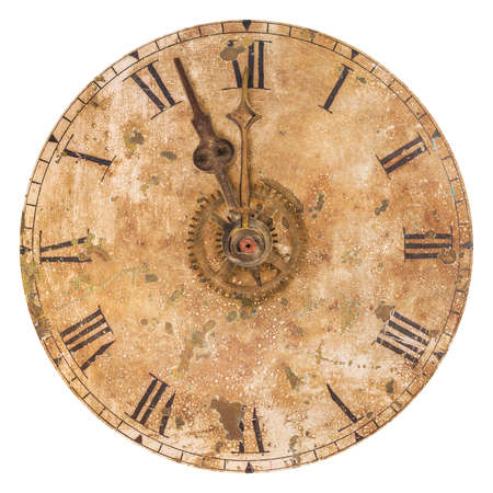 Vintage and heavily weathered clock face with time set to a few minutes to twelve o clock isolated on a white background