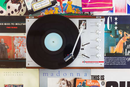 Dieren, The Netherlands - October 7, 2020: Vintage record player with spinning record on a background of old pop music records and singles in Dieren, The Netherlands Editoriali