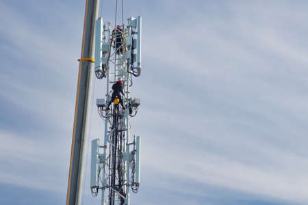 Assembly of a new 5G network telecommunications tower with two technicians in The Netherlands