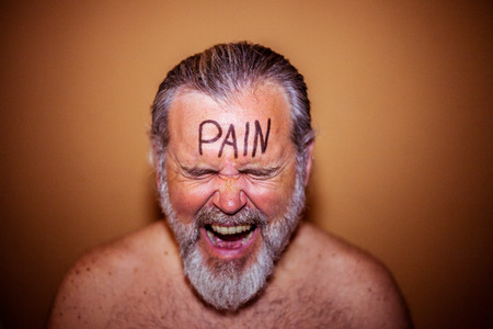Portrait of a shirtless man with the word pain written on the forehead