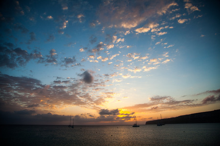 Maritime landscape at dawn with some boats in the background and an expressive sky with clouds Stock Photo