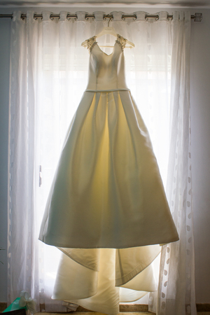 Wedding dress hanging from the curtain of the bride on her wedding day