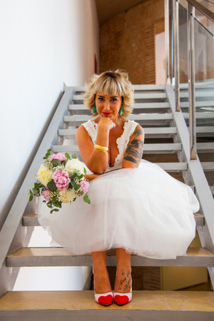 Beautiful bride sitting on a ladder with her bouquet with a funny gesture