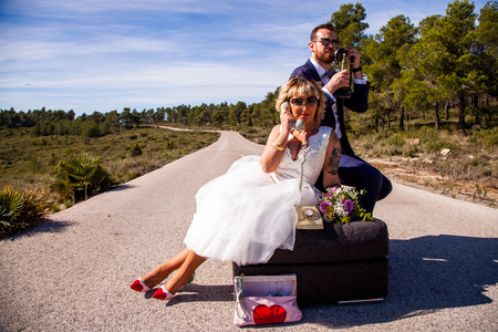 Newlywed couple on their sofa in the middle of a lonely road with vintage phones