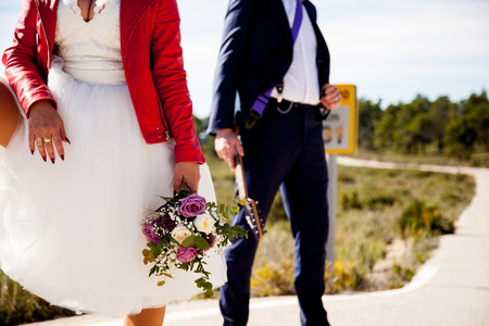A woman dressed as a bride, with a red jacket and a bouquet, waits next to a man dressed in a suit and an electric guitar on a lonely road.