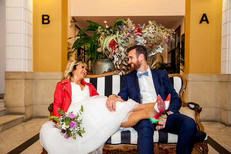 Couple of newlyweds sit on a hotel reception sofa.