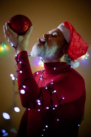 A lewd Santa Claus licks with his tongue a round red Christmas ornament 版權商用圖片