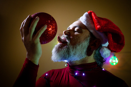 A lewd Santa Claus licks with his tongue a round red Christmas ornament Stock Photo
