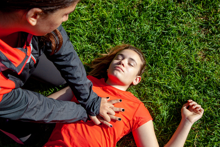 Two young girls practicing cardiopulmonary resuscitation maneuvers in an open-air park