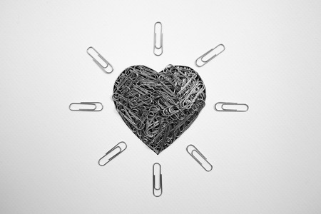 Heart shape made with paperclips on white background