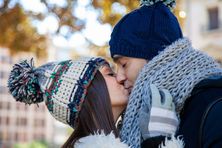 Young couple dressed in winter clothes and wool hats kissing passionately in a public park Reklamní fotografie