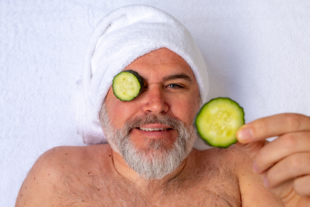 A man with cucumber slices over his eyes makes a funny gesture while receiving a beauty treatment in a salon.
