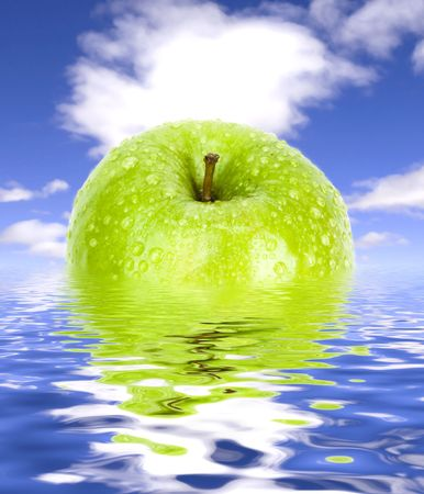 green apple with drops on background of water and sky Stock Photo