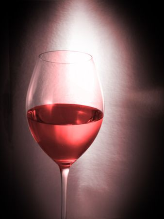 Glass of rose wine on black background