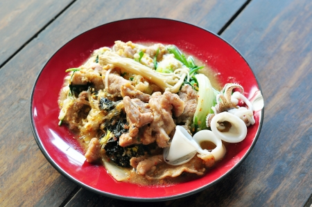 Sukiyaki with pork and squid, Asian cuisine, on wooden table photo