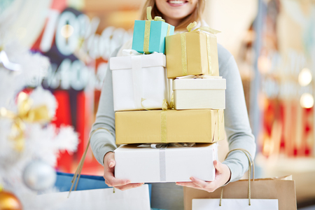 heap: Woman holding pile of Christmas gift boxes and paper bags