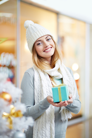 heap: Beautiful young woman wearing a knit hat and a scarf holding a small gift box