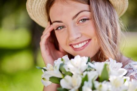 girl holding flower: Charming smiling girl holding flower bouquet in summer