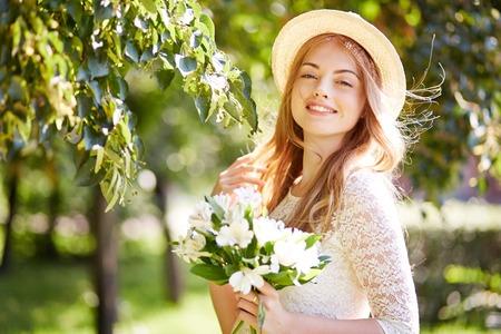 girl holding flower: Elegant girl holding flower bouquet among trees