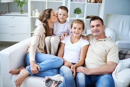 family  room: Loving family of four sitting on sofa in living room