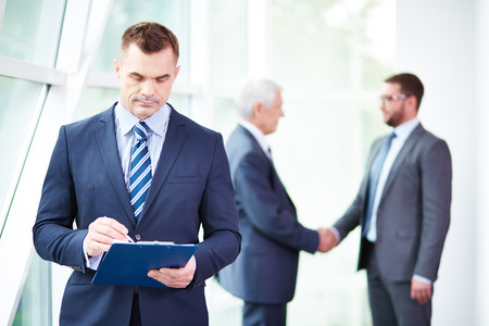 3 persons only: mid adult businessman working with documents while his colleagues shaking hands behind him