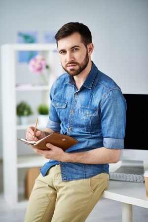 rolledup sleeves: Handsome man writing down his appointments in personal organizer
