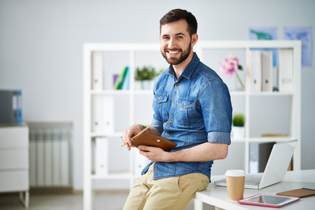 rolledup sleeves: Attractive designer sitting on table in studio holding appointment book Stock Photo
