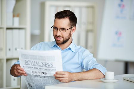 rolledup sleeves: Young businessman reading morning newspaper in office