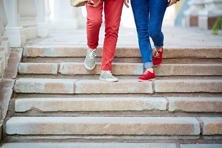 bajando escaleras: Las piernas de la joven pareja al bajar escaleras