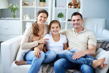 family  room: Portrait of happy family sitting on sofa in living room
