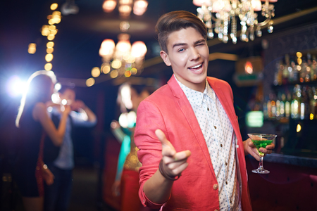 charismatic: Charismatic young man in coral jacket having a good time in night club and pointing at you