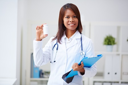 southeast asian: Southeast Asian female doctor showing bottle of pills  Stock Photo