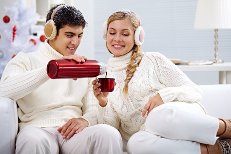 muff: Portrait of happy young couple drinking hot tea at christmas