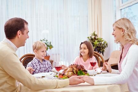 family praying: Lovely family of four praying before Thanksgiving dinner