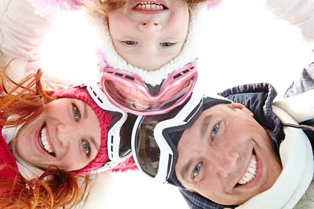 directly: Directly below shot of positive family wearing ski goggles