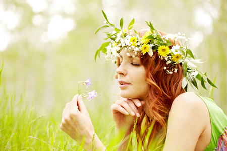 woman resting: Portrait of a beautiful red-haired girl reclining on grass and smelling a wildflower Stock Photo