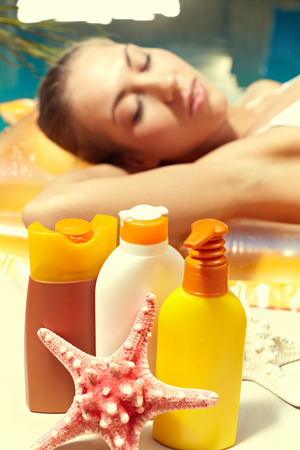 sun screen: Sun screen toiletries with a relaxing woman in the background