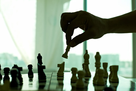 pawn adult: Hand playing chess in the dark closeup Stock Photo