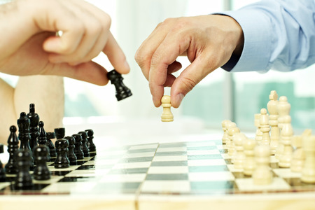 pawn adult: Hands moving chess pieces on board coseup Stock Photo
