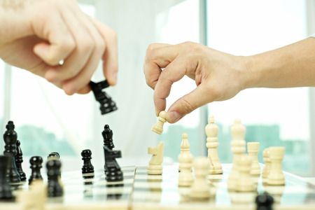 pawn adult: Two people competing in chess play closeup Stock Photo