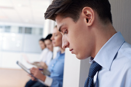 peer pressure: Close-up of profile of student sitting separately from his peers