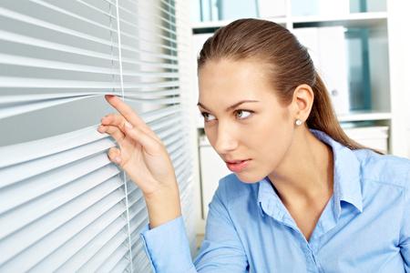 jalousie: Young businesswoman peeping through jalousie in office
