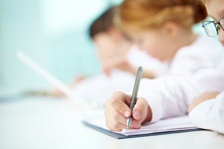 workbook: Close-up of child writing in his workbook