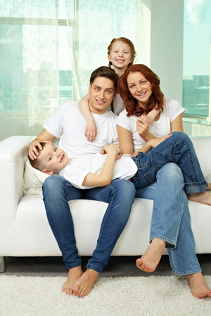 sofa: Portrait of happy family sitting on sofa and embracing each other